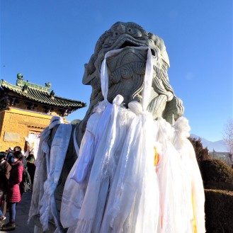 Snow lion covered in Khata scarves