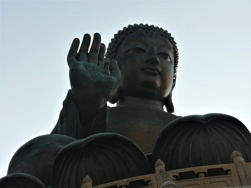 The Buddha's right hand is raised, representing the removal of affliction, while the left rests open on his lap in a gesture of generosity.